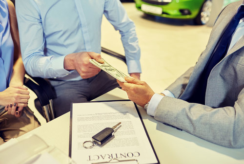 customers giving money to car dealer in auto salon