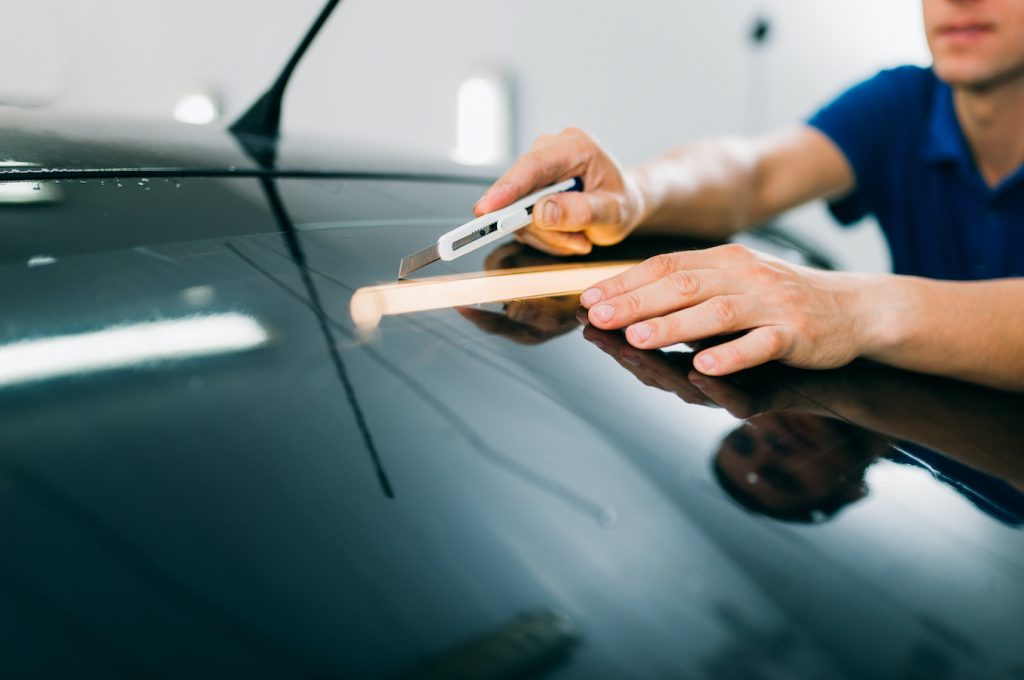 Male worker with blade, car tinting film installation process, tinted auto glass installing procedure