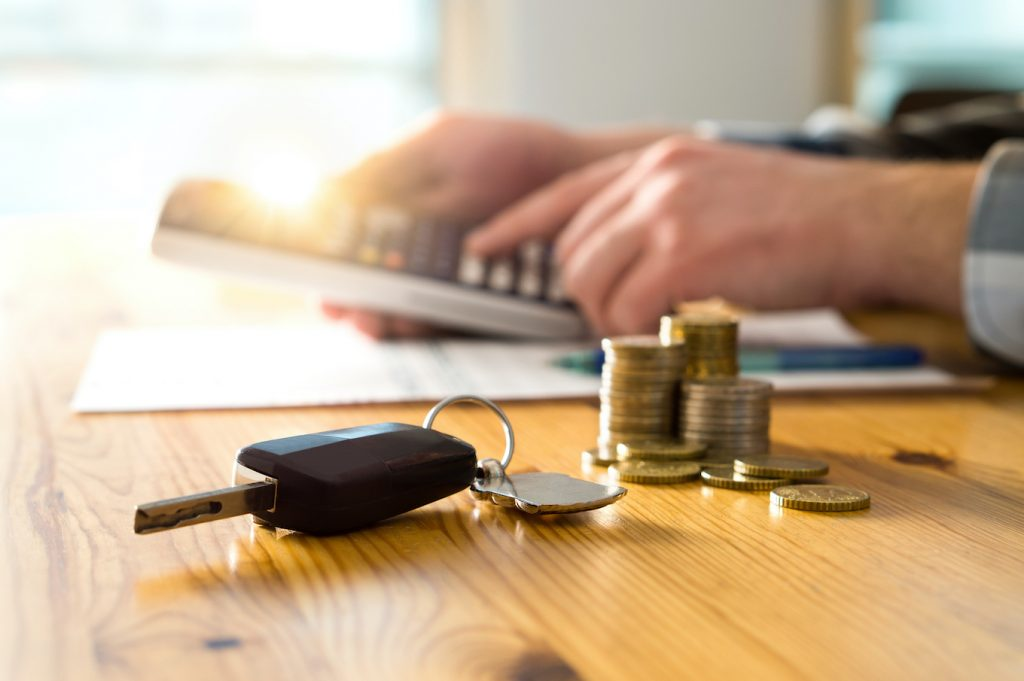 Car keys and money on table with man using calculator. Buyer counting savings and gas cost or salesman calculating sales price, vehicle value or road taxes.