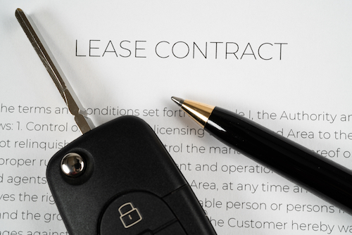 Pen and car key on top of a lease contract ready to be signed