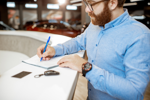 Young man signing some documents, buying or renting a car in the modern showroom of the car dealership