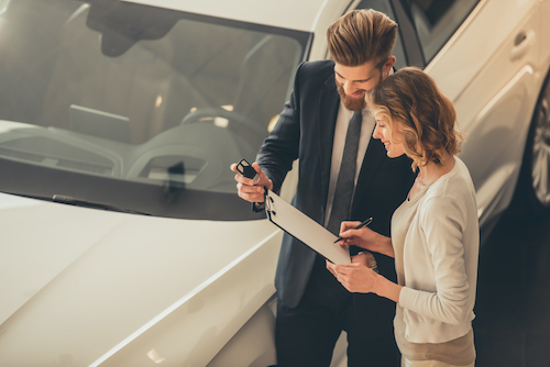 Beautiful young woman is signing a document and talking to handsome bearded sales manager while buying a new car in dealership