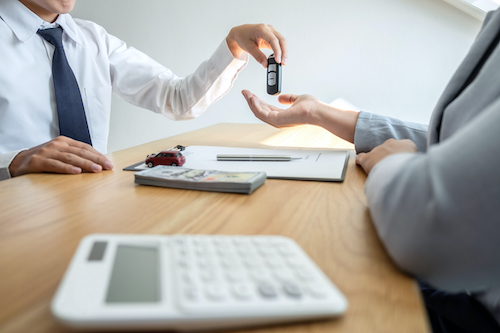 Car rental and Insurance concept, Young salesman giving car's key to customer after sign agreement contract with approved for rent or purchase.