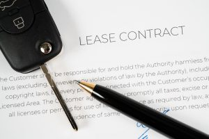 Pen and car key on a lease contract ready to be signed
